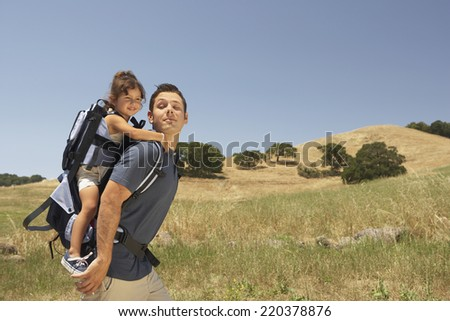Young man carrying his daughter in a backpack outdoors - stock photo