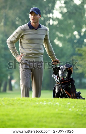 Young man carrying trolley with golf bag - stock photo