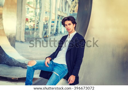 Young Man Casual Street Fashion. American college student, wearing fashionable long coat, jeans, sitting against metal mirror wall in New York, looking at you, thinking. Instagram filtered effect.  - stock photo