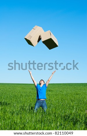 young man catching boxes on green field - stock photo