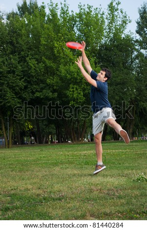 young man catching frisbee outdoors - stock photo