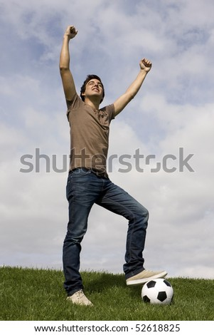 Young man celebrate something with his arms up - stock photo