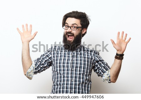 young man celebrating victory over white. Crazy nerd man wearing eyeglasses win and shouting while raising his hands - stock photo
