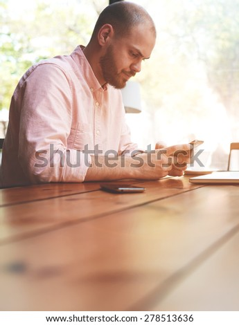 Young man chatting on his smart phone while sitting at wooden table with blur copy space for your text message, male student sitting at modern university library, business man using cell phone working - stock photo