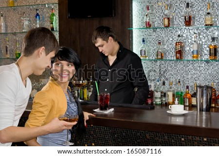 Young man chatting up a woman at the bar approaching her from behind with a drink in his hand as they both enjoy happy hour at the pub - stock photo