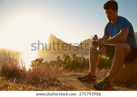Young man checking his sports watch - stock photo