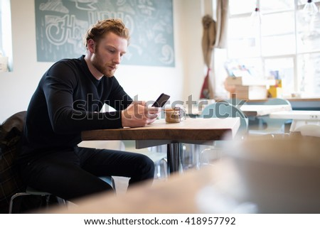 Young Man Checking Mobile Phone In Coffee Shop - stock photo