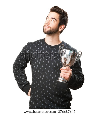 young man cheering with a trophy - stock photo
