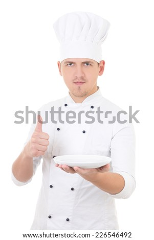 young man chef  in uniform thumbs up and showing empty plate isolated on white background - stock photo