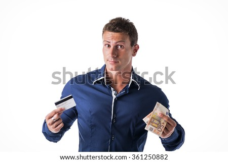 Young man choosing: banknotes or credit card