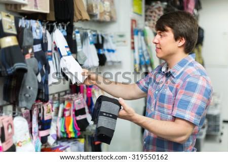 Young man choosing socks at the shop and smiling - stock photo