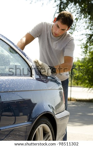 Young man cleaning a car with sponge - stock photo