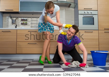 Young man cleaning floor and looking at her girlfriend - stock photo