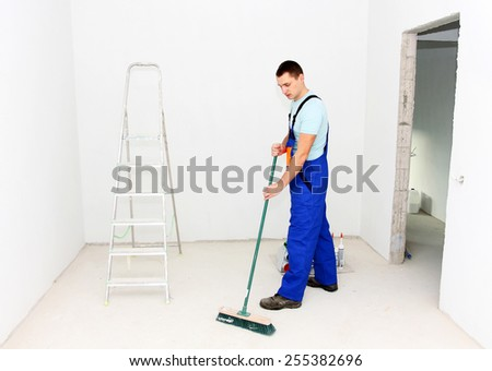 Young man cleaning floor with brush after repair - stock photo