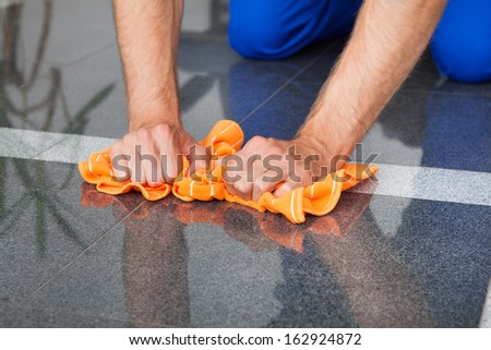 Young Man Cleaning The Dust On Floor With Duster - stock photo