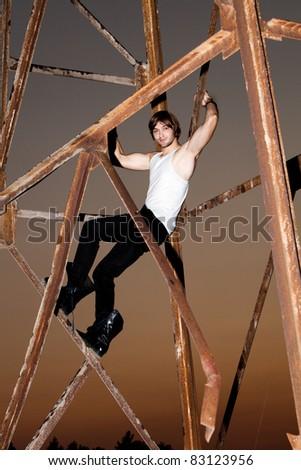 young man climb on big metal construction, outdoor night - stock photo