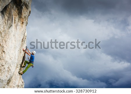 Young man climbing natural rocky wall - stock photo