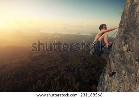 Young man climbing natural rocky wall at sunrise - stock photo