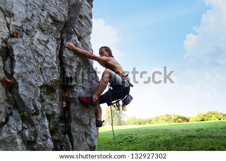 Young man climbing natural rocky wall with blue sky on the background