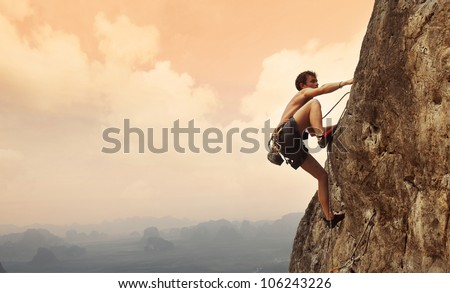 Young man climbing on a limestone wall with wide valley on the background - stock photo