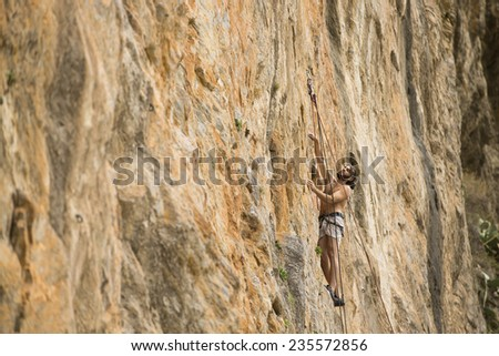 Young man climbing on a wall - stock photo