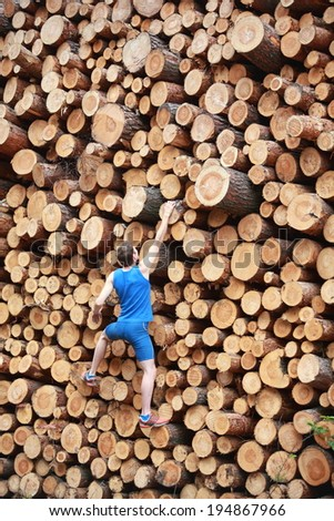 Young man climbing the large pile of cut wooden logs - back view - stock photo