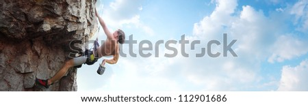 Young man climbing vertical wall with belay with blue cloudy sky on the background - stock photo