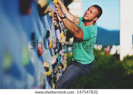 young man climbing wall rock outdoors - stock photo