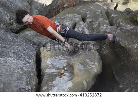 Young man climbs on a cliff with a rope.