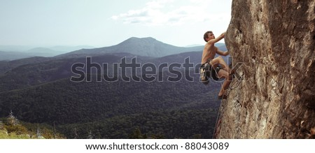 Young man climbs on a rocky wall in a valley with mountains - stock photo