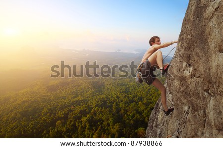 Young man climbs on a rocky wall in a valley with mountains at sunrise - stock photo
