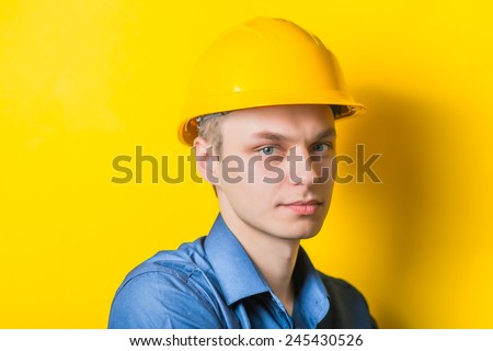 Young man close-up in yellow construction helmet and a blue shirt on a yellow background looking at the camera. Mimicry. Gesture. photo Shoot - stock photo