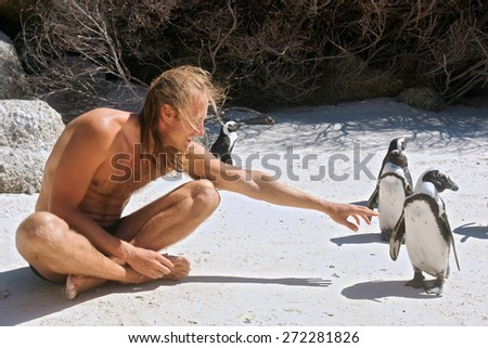 Young man communicates with penguins. Shot in the Boulders Beach Nature Reserve, near Cape Town, Western Cape, South Africa.  - stock photo