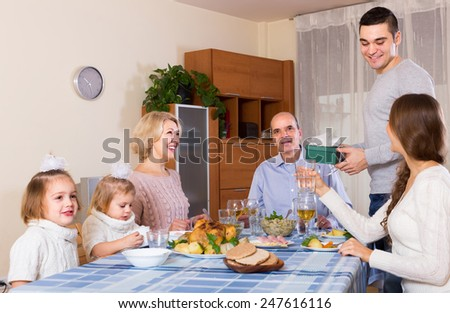 Young man congratulating heartily family member at the table at home
