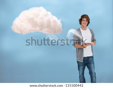 Young man connecting to cloud computing via tablet pc - stock photo