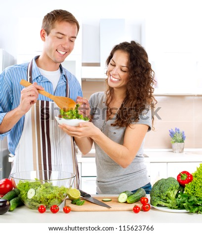 Young Man Cooking. Happy Couple on a Kitchen at Home Eating Fresh Vegetable Salad.Diet.Dieting. Loose Weight Concept - stock photo