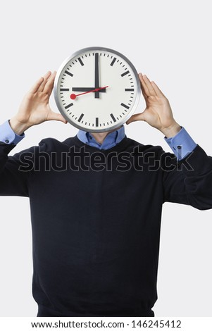 Young man covering his face with clock standing against white background