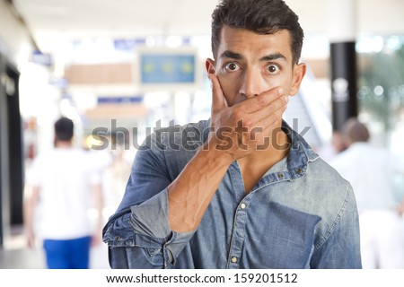 young man covering his mouth in a shopping center - stock photo