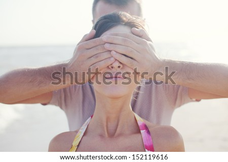 Young man covering the eyes of his girlfriend on the beach during summer time fun outdoors - stock photo