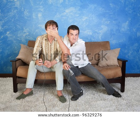 Young man covers face of friend while playing video games - stock photo