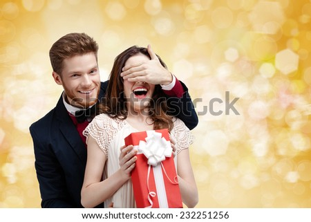 Young man covers with hand eyes of his girlfriend, yellow background - stock photo