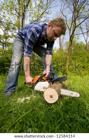Young man cutting wood - stock photo