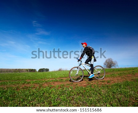 Young man cycling on a rural spring road at sunny day