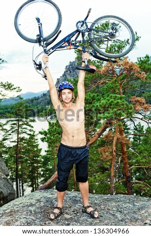Young man cyclist holding his bicycle on the top of a hill. - stock photo
