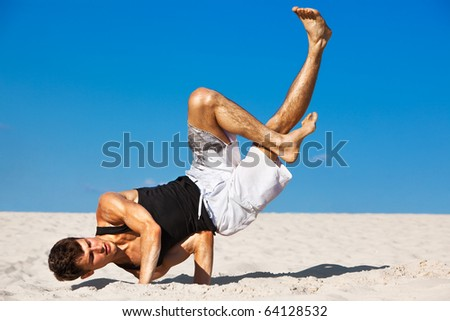 Young man dancing on beach. - stock photo