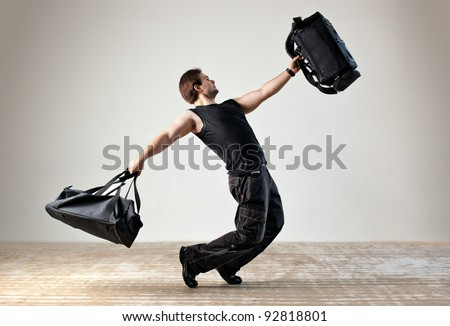 Young man dancing with bags. - stock photo
