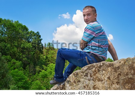 Young man dangerously sitting at the edge of the cliff and enjoying the picturesque view - stock photo