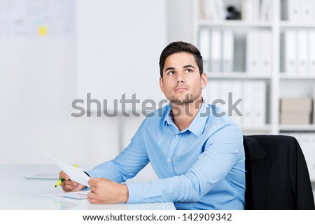 Young man daydreaming in the office sitting at his desk with a document in his hands staring up into space lost in thought