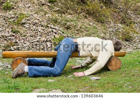 Young man deeply sleeping or drunk, laying outdoors on a wooden park bench. Profile view - stock photo