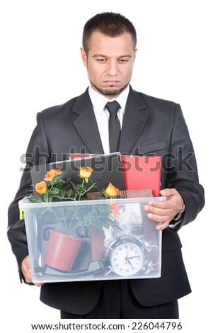Young man dismissed from his job. He is keeping basket with things. - stock photo